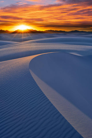 Sun setting behind the hills and windswept sand dunes at White Sands National Monument New Mexico