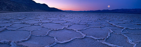 Full moon over the salt flats of Death Valley California at sunrise