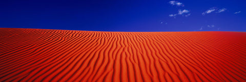 Bright orange windswept sand dunes of Simpson Desert Australia with a blue sky above