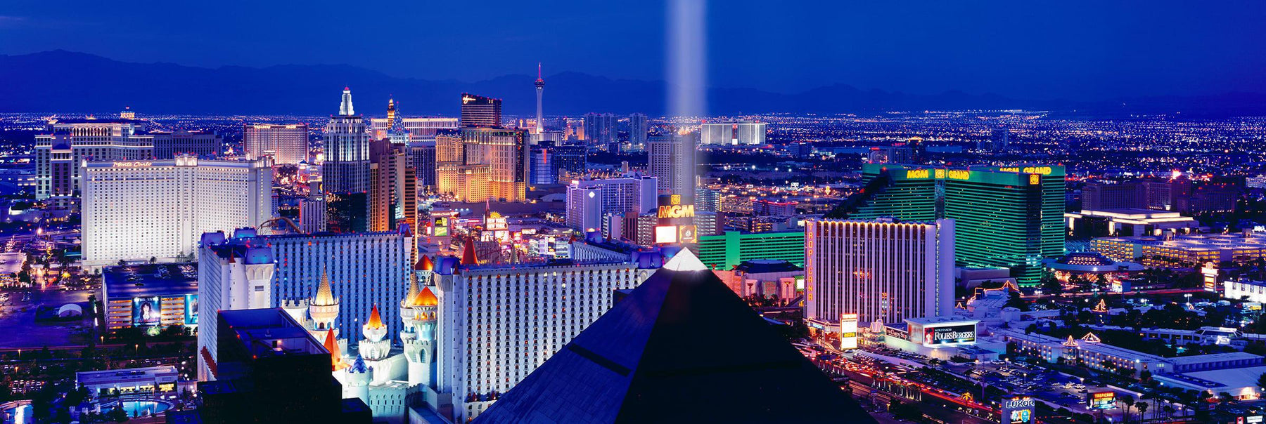 Rooftop view of the Las Vegas Strip and the Luxor pyramid shining into the sky at night