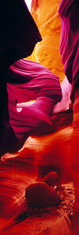 Two boulders sitting in the red orange and pink sandstone canyon of in Antelope Canyon Arizona