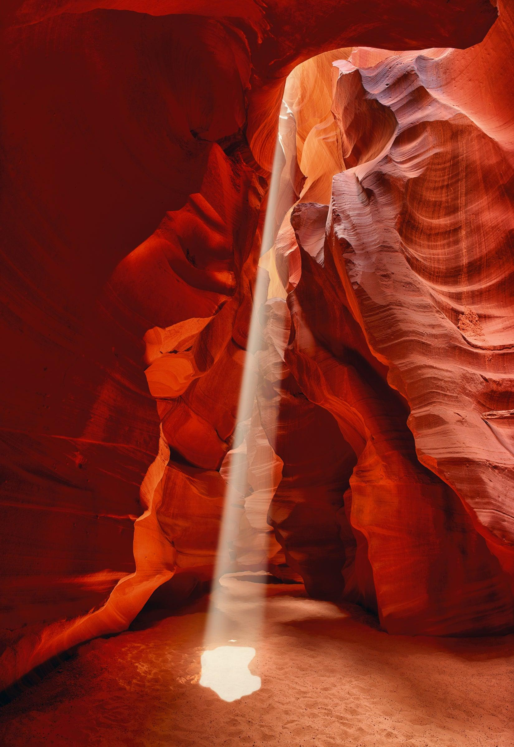 Sun light shining through the ceiling and onto the sand floor of the slot canyons in Antelope Canyon Arizona