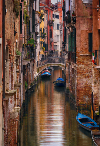 Boat filled canal surrounded by old buildings in Venice Italy at midday