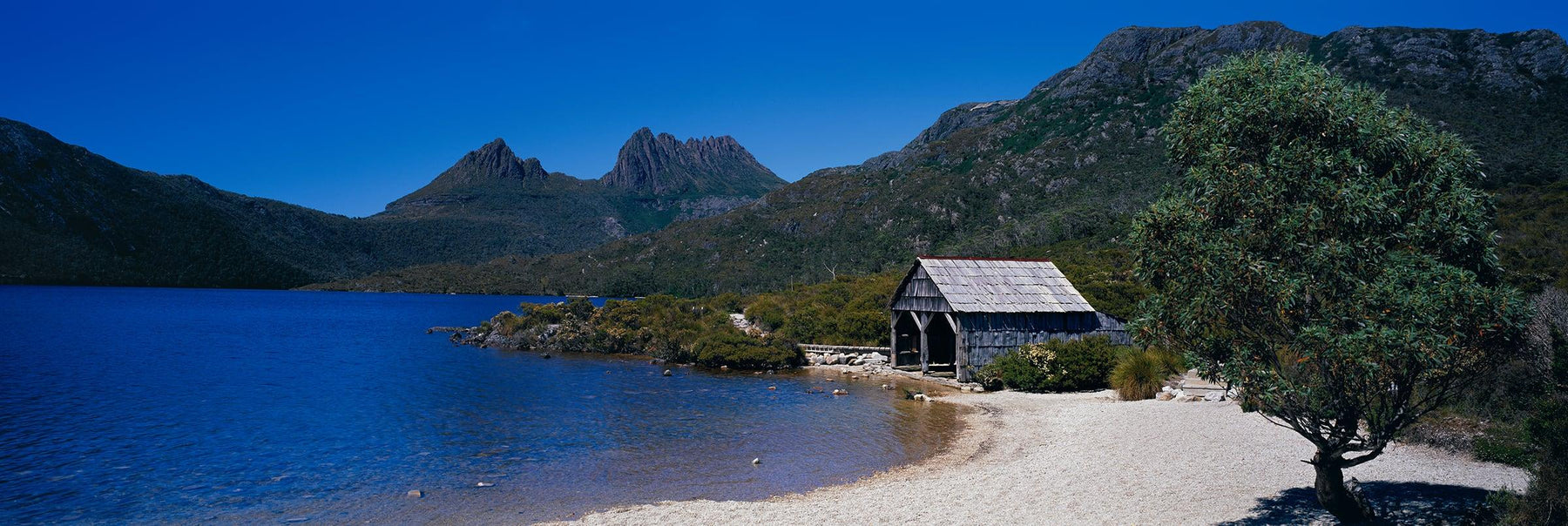 Old wooden boathouse on the sandy shores of Dove Lake in Australia