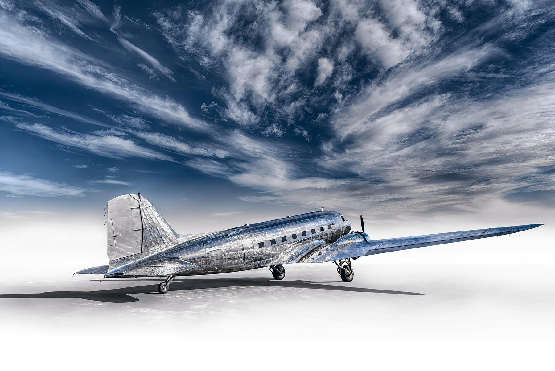 Silver DC-3 airplane with a white foreground and a cloudy blue sky above