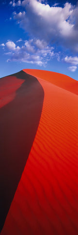 Red windswept sand dunes under cloudy blue skies in Coral Pink Sand Dunes Utah