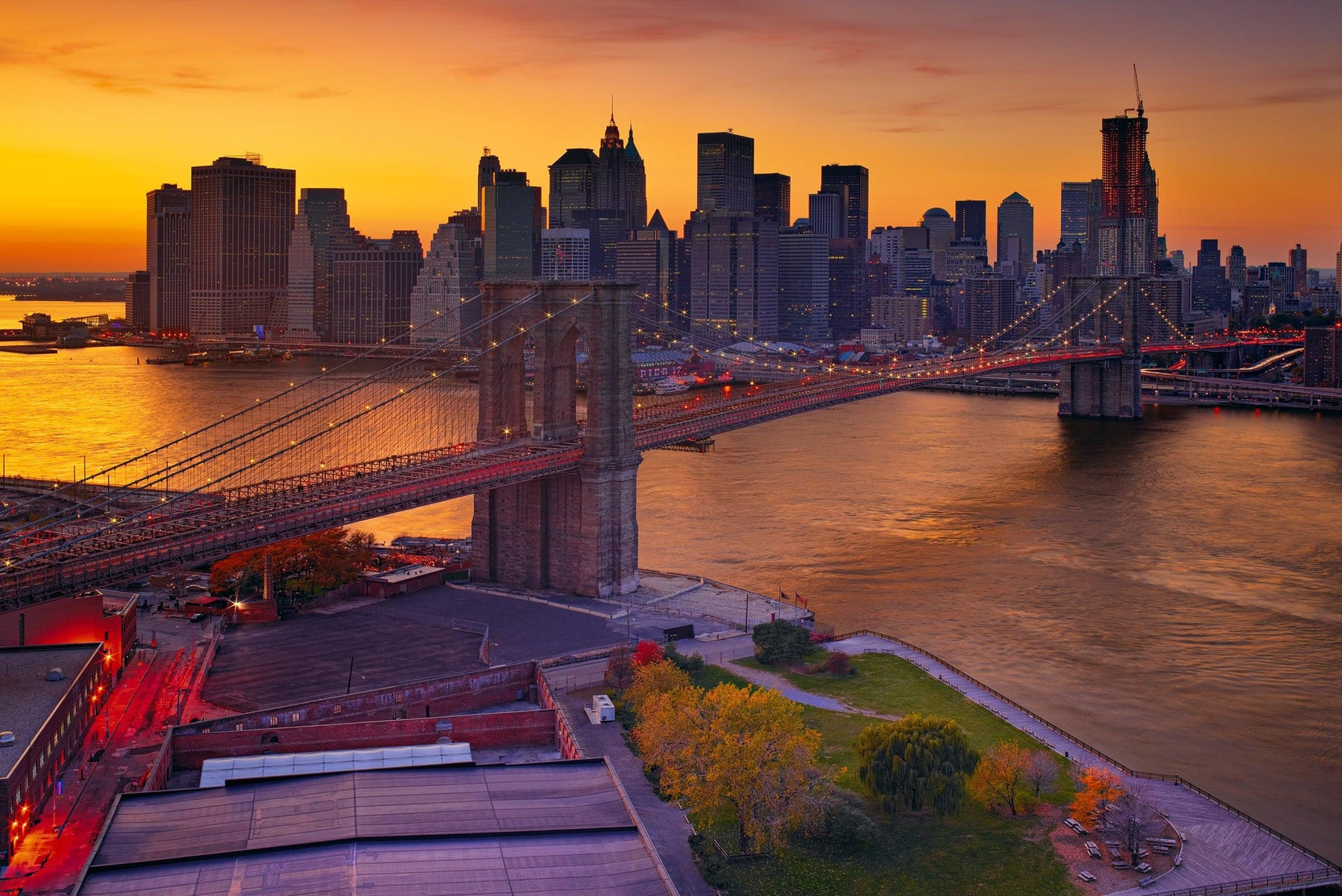 Rooftop view of the Brooklyn Bridge at sunset leading over the East River into Brooklyn New York