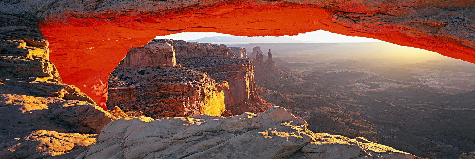 Sun shining through the rock arch that overlooks the valley of Canyonlands National Park Utah