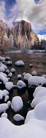 Snow covered rocks on the edge of the river running through Yosemite Valley with El Capitan mountain in the background