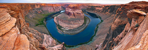 Looking down from a steep cliff into a horseshoe shaped river at Horseshoe Bend Arizona