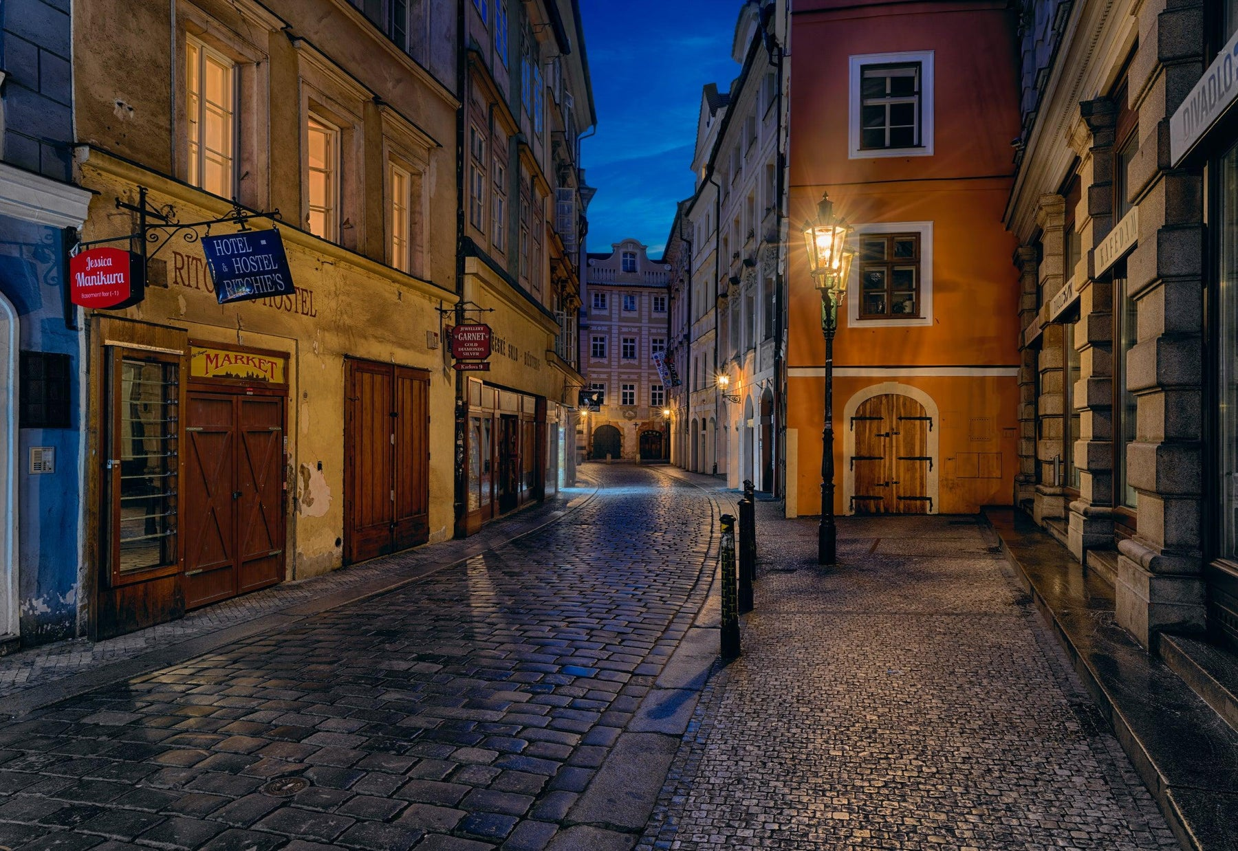 Stone brick street leading through the old lamp lit buildings of Prague Czech Republic