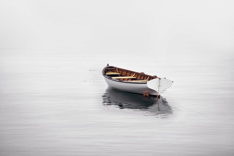 White wooden rowboat floating in the calm waters and misty cove in Martha's Vineyard Massachusetts