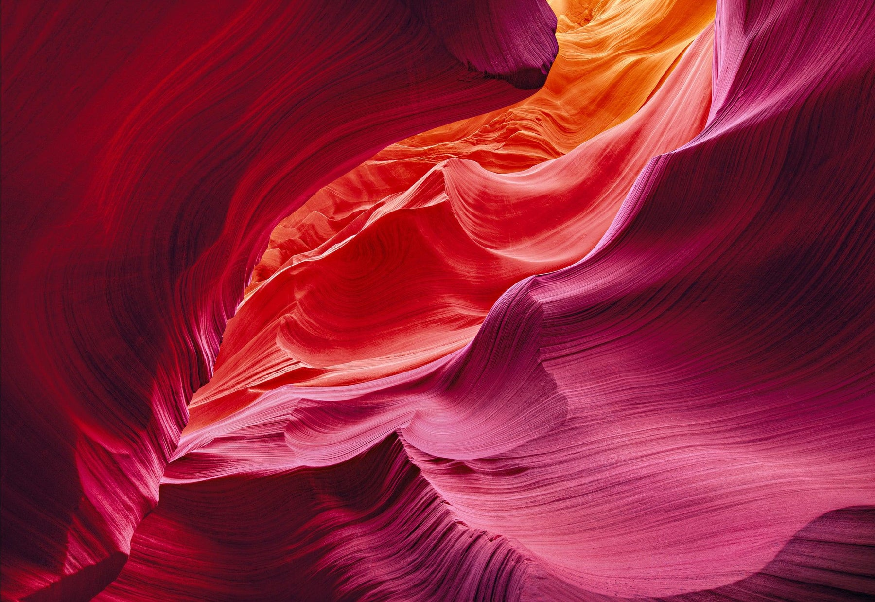 Red orange yellow and pink wave shaped sandstone walls of the slot canyons in Antelope Canyon Arizona