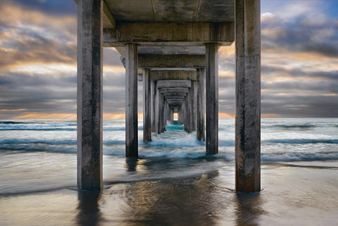 Waves crashing under the pier and onto the beach in La Jolla California on a stormy day