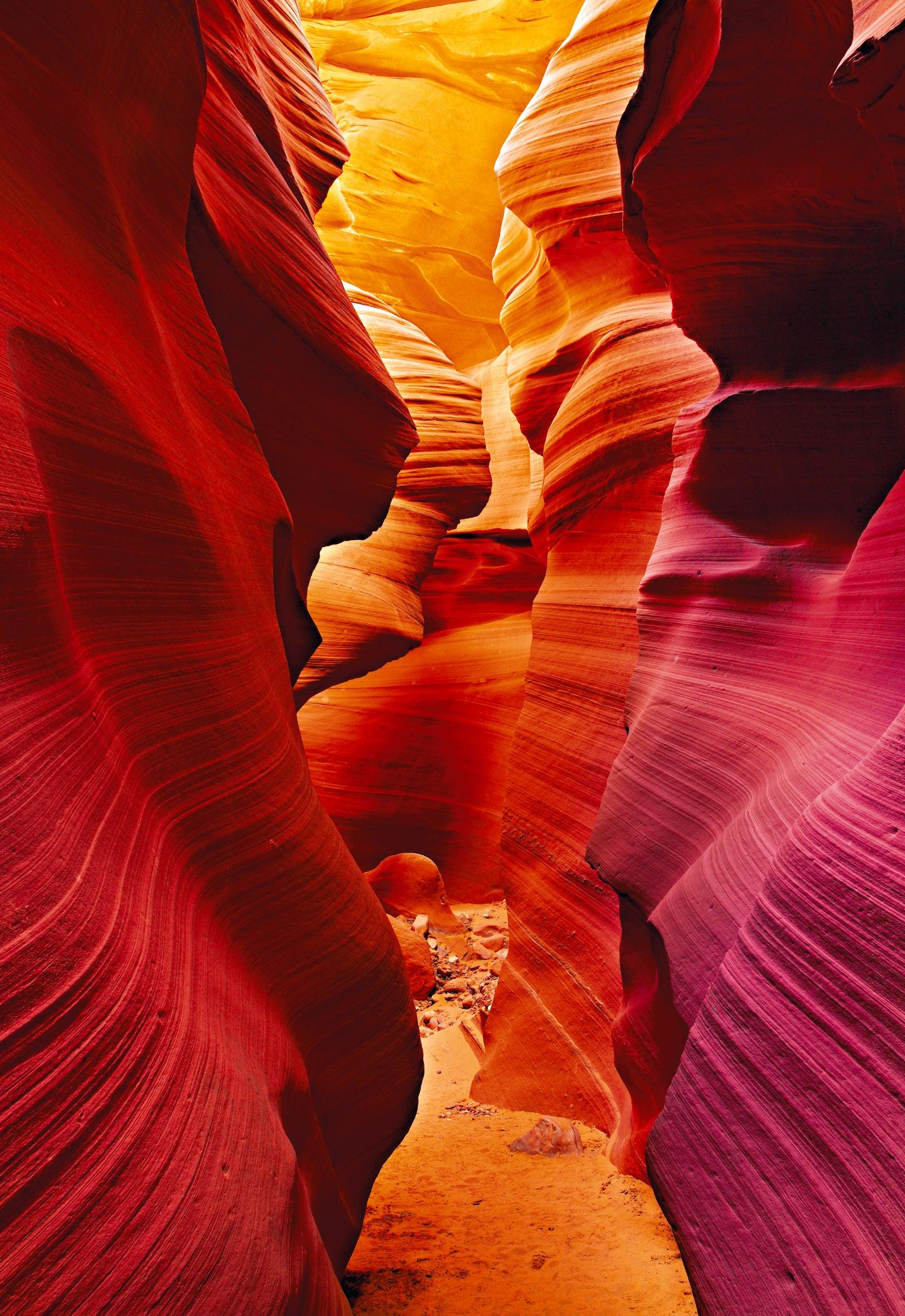 Sand path through the red orange and pink sandstone walls of the slot canyons in Antelope Canyon Arizona