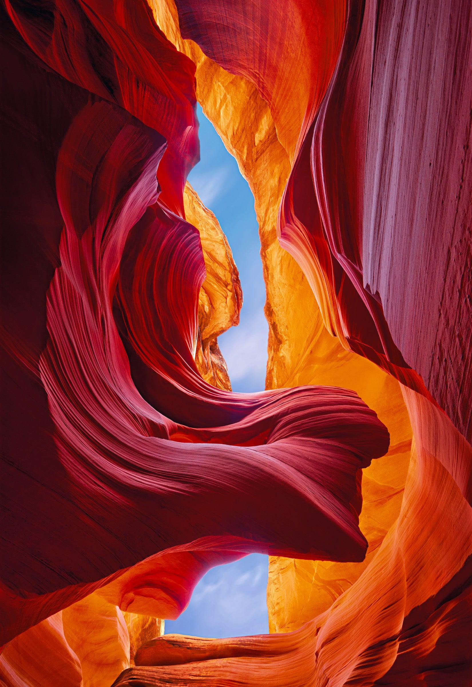 Looking up at the blue sky through the pink red and orange sandstone walls of Antelope Canyon Arizona