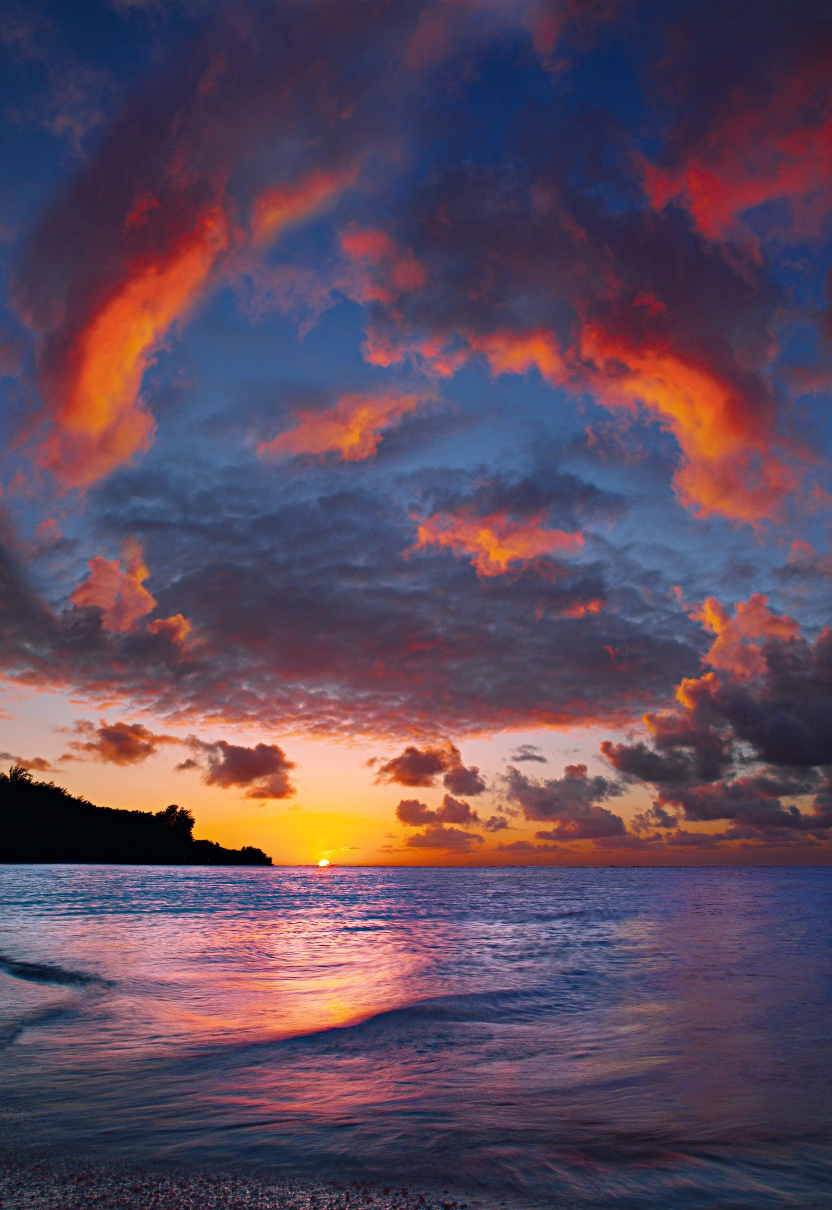 Swirl of clouds reflecting into the Hawaiian ocean at sunset with the cliffs of Na Pali Coast in the background
