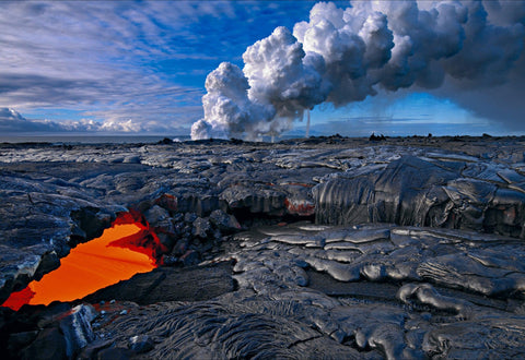 Lava showing through a hole in a lava field on the shore of Kilauea Hawaii with a towering cloud of smoke in the background