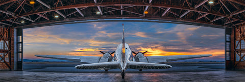 Silver DC-3 airplane in the middle of an open metal hanger in Aurora Oregon looking out to a cloudy sky at sunset