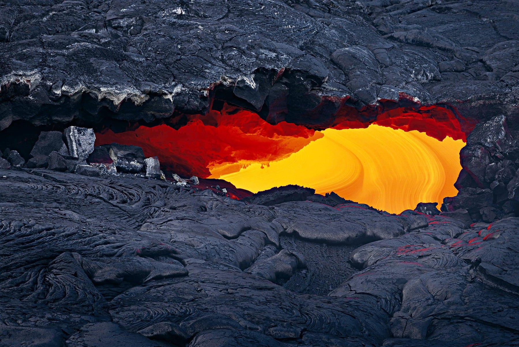Close up of lava showing through a hole in a black lava field of Kilauea Hawaii