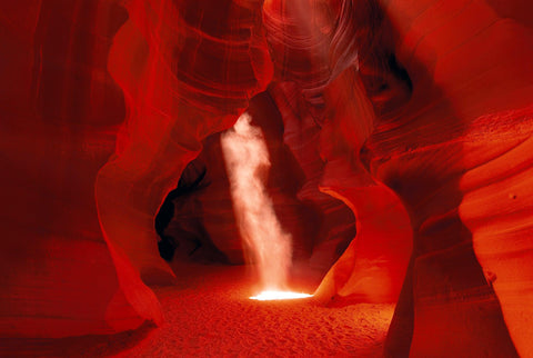 Sun shining into dust in the shape of a ghost within the sandstone walls of the slot canyons in Antelope Canyon Arizona
