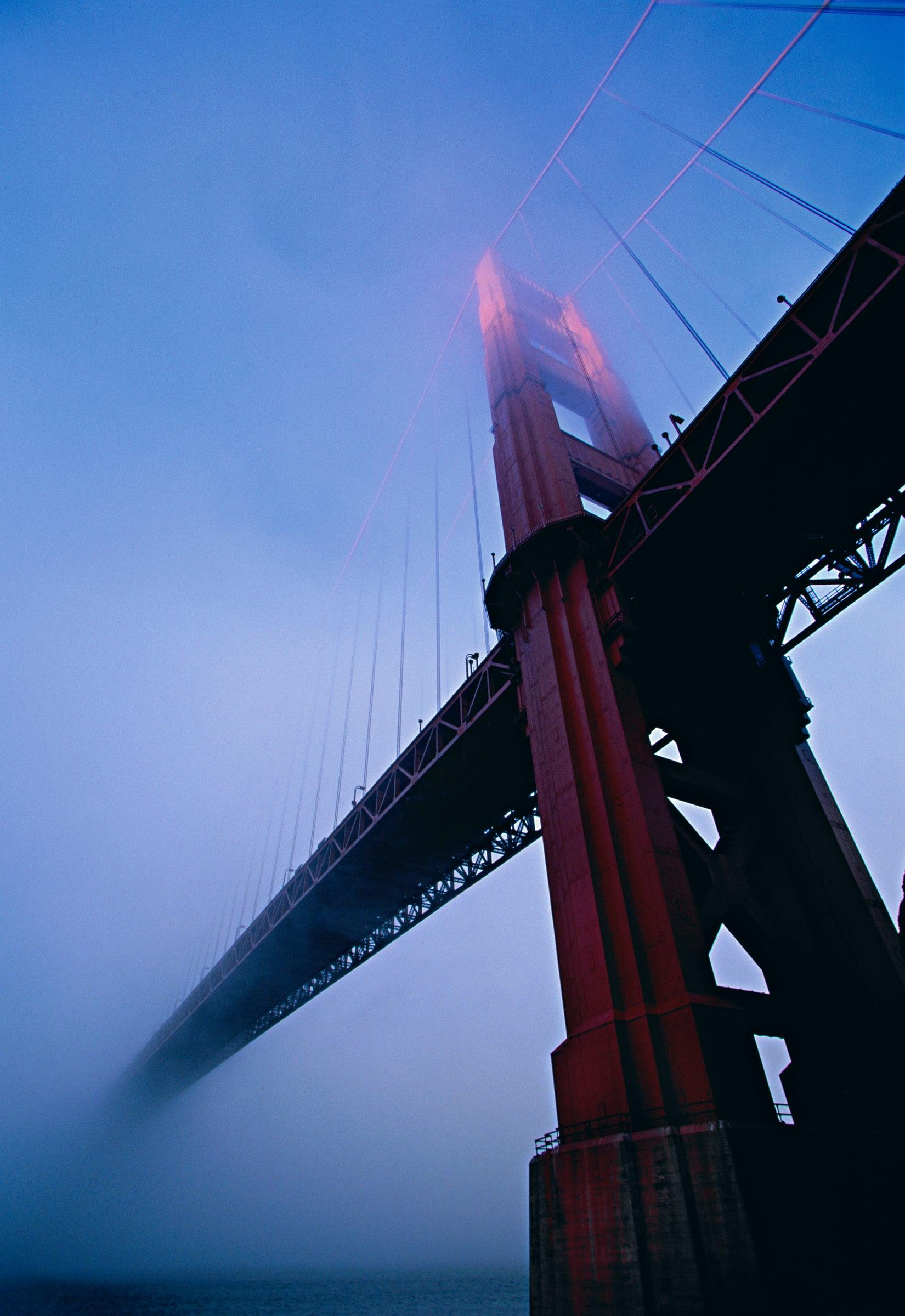 View looking up from under the Golden Gate Bridge in San Francisco covered with fog