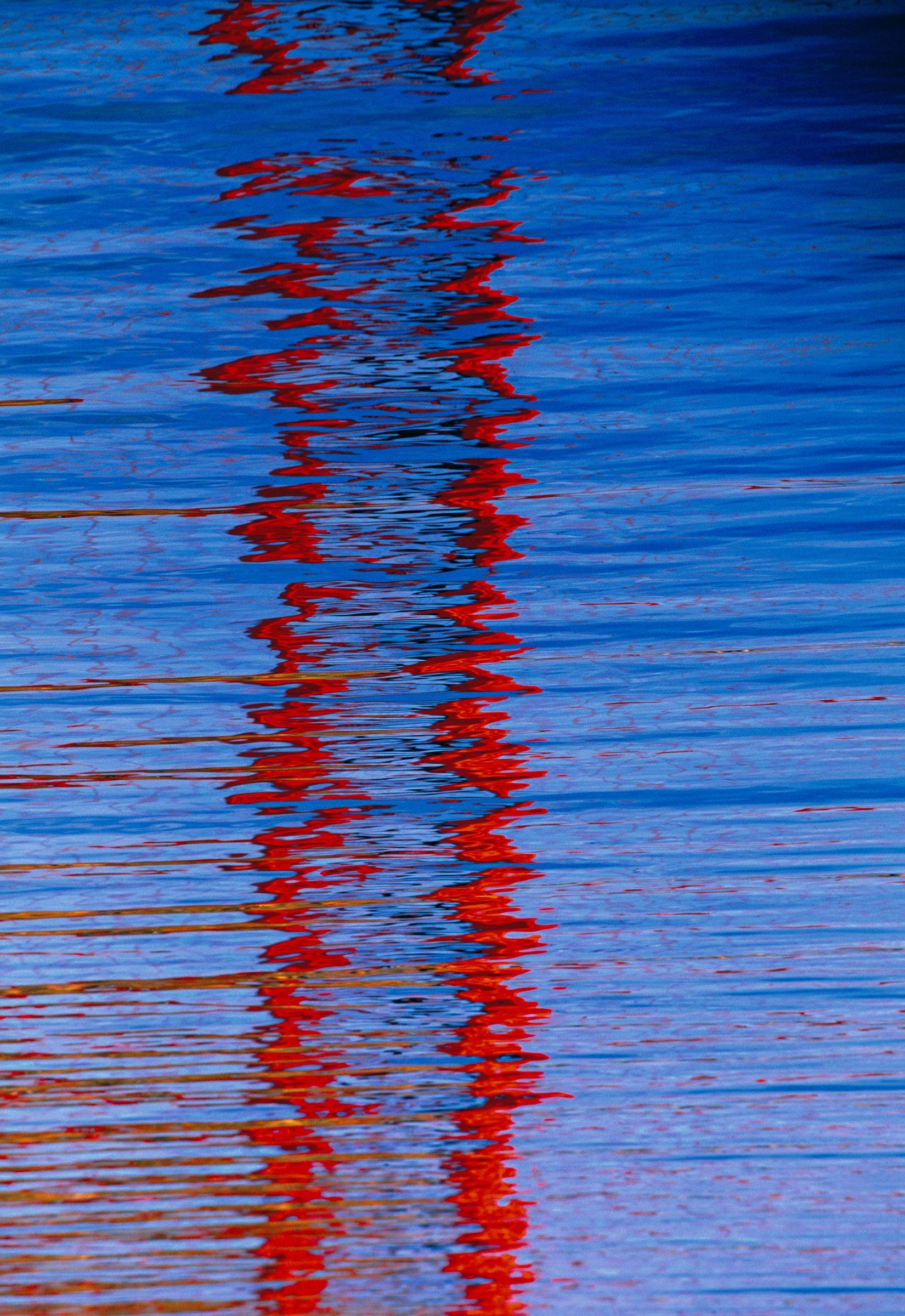Close up of the Golden Gate Bridge tower reflecting into the waters of Horseshoe Bay