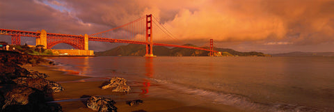 Rock and sand beach looking back at the Golden Gate Bridge during a cloud filled sunset