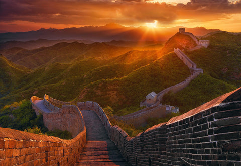 Brick pathway down the Great Wall of China over tree covered hills into the sunset in the background