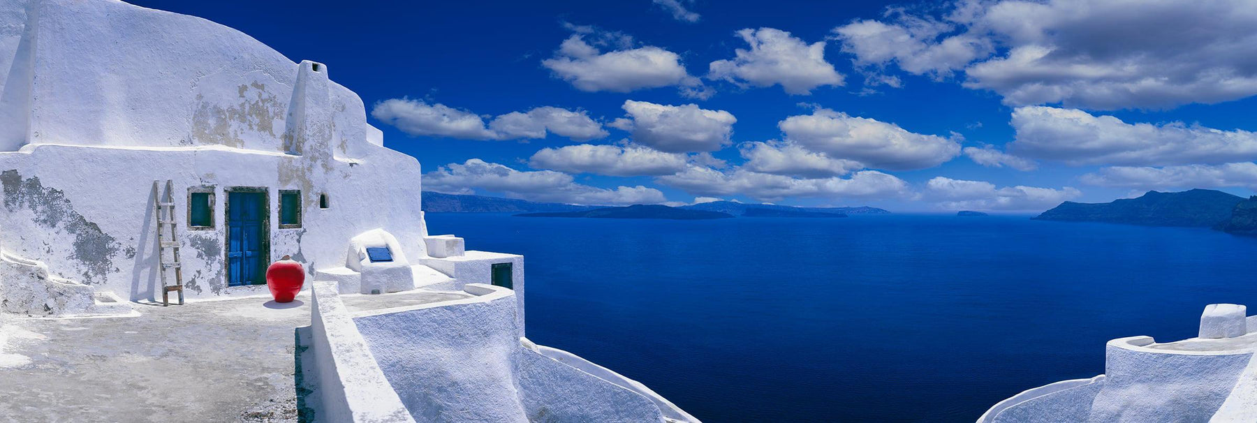White plastered house and courtyard overlooking the blue ocean and cloudy skies of Santorini Greece