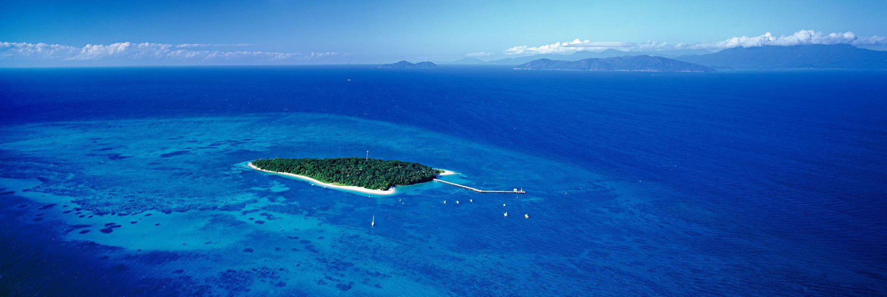 Aerial view of Green Island full of trees with a pier and boats surrounded by the Great Barrier Reef Australia