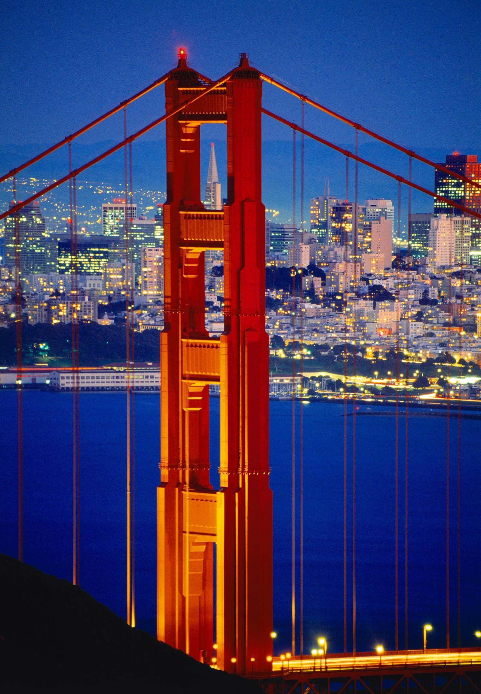 Close up of one of the Golden Gate Bridge towers at night with San Francisco lit up in the background