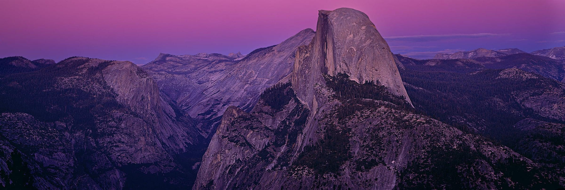 Granite dome rock formation surrounded by the mountains and forest of Yosemite National Park California
