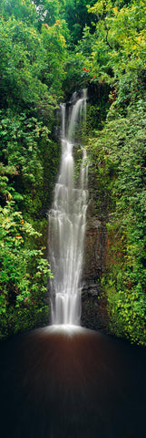 Waterfall pouring out of a tropical rainforest into a dark black pool on the road to Hana Hawaii