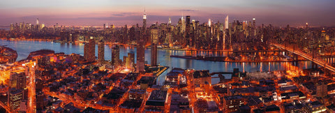 View of New York City from a rooftop lit up at night with the streets glowing orange and red