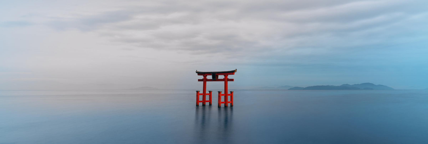 Red Torii gate standing in a calm blue lake in Japan with hills in the background