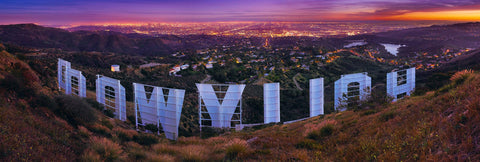 View from behind the Hollywood sign looking down over Los Angeles lit up at sunset