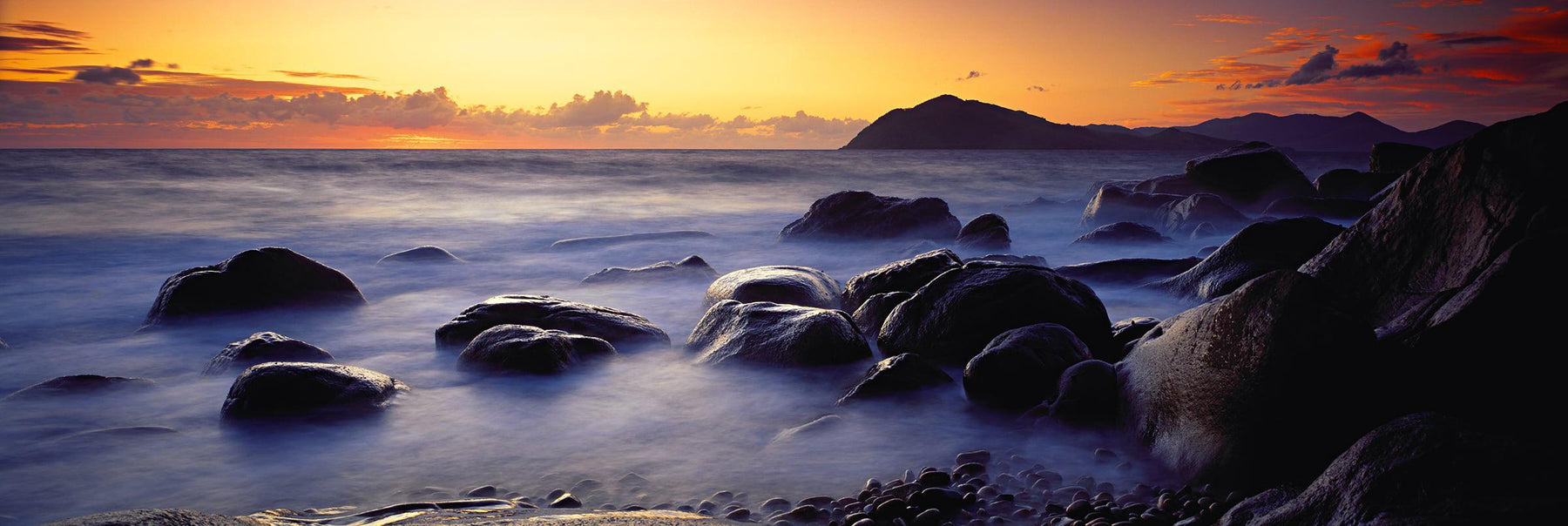 Rock beach being hit gently by waves at Orpheus Island Australia at sunrise