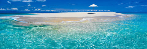 Umbrella stuck in the white sand of the Upolu Cay in the middle of the Great Barrier Reef in Queensland Australia