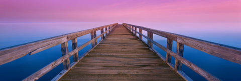 Old wooden pier reaching over the ocean into a pink and purple horizon during a sunrise in Port Mahon Delaware