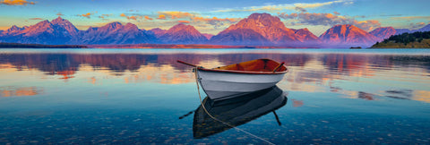 White wooden row boat floating along the shore of Jackson Lake Wyoming with the sun shining on the mountains behind