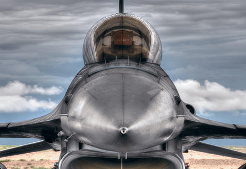 Close up of the front end and cockpit of a F-16 fighter jet with storm clouds behind