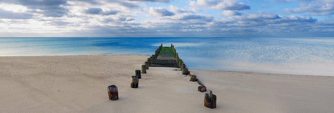 Wooden jetty half buried by the sand beach stretching out over the ocean in Cape Cod Massachusetts
