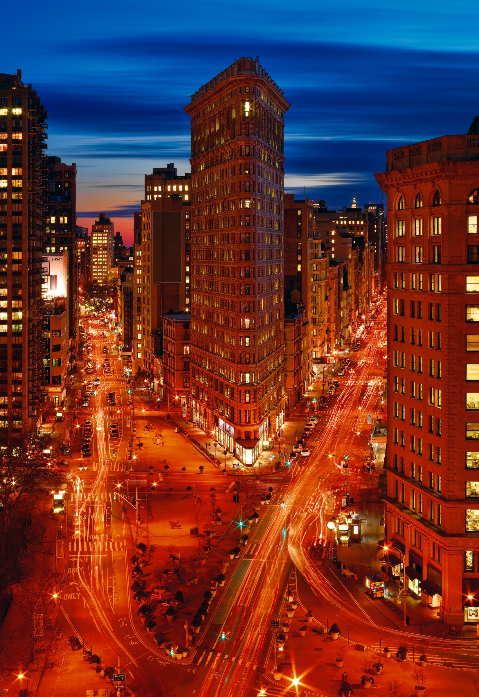 Flat Iron building at night and the glowing lights of moving cars in the street below in New York City