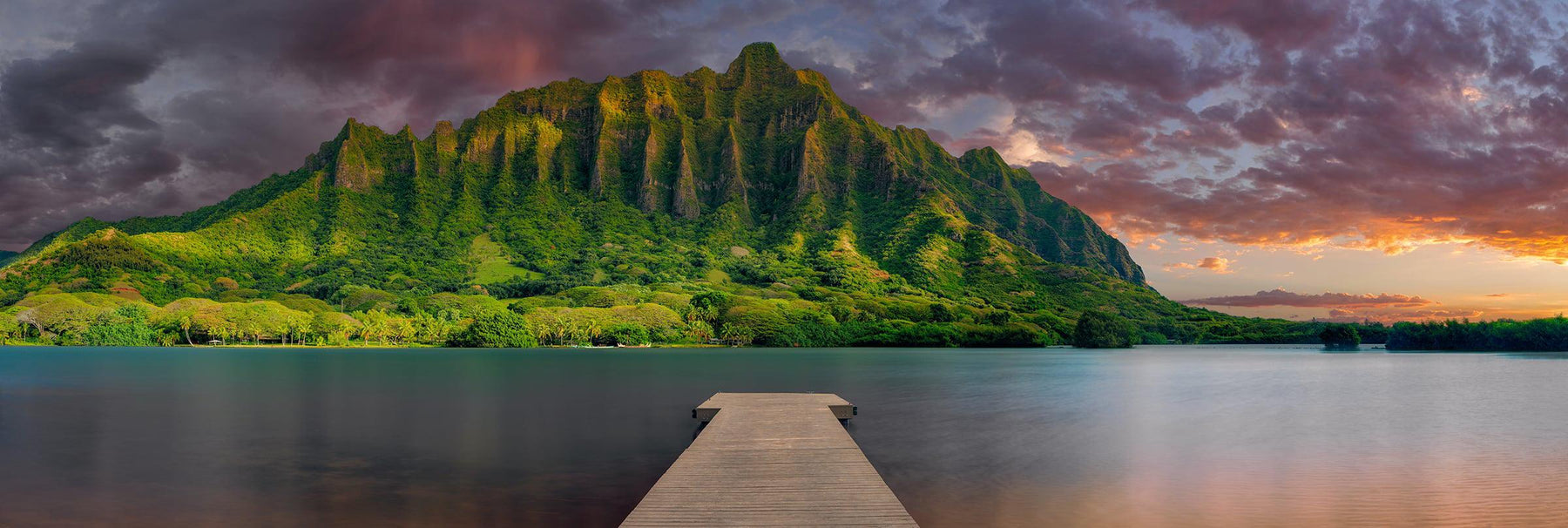 Wood jetty stretching over a lagoon with the sun setting behind the tropical mountain cliffs of Oahu Hawaii