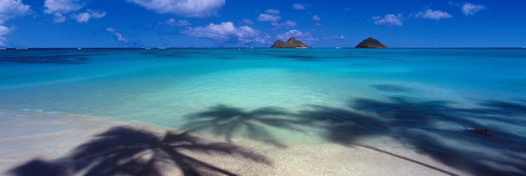 Palm tree shadows on the white sand beaches of Lanikai Hawaii with two islands in the background