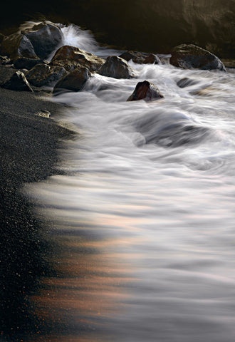 Water crashing over the black sand beach and rocks on the coast of Kona Hawaii