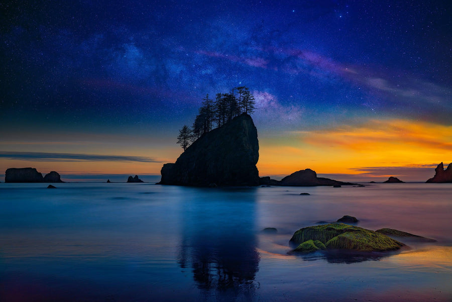 Silhouette of a sea stack covered with trees reflecting off the beach at sunset with the stars and milky way behind