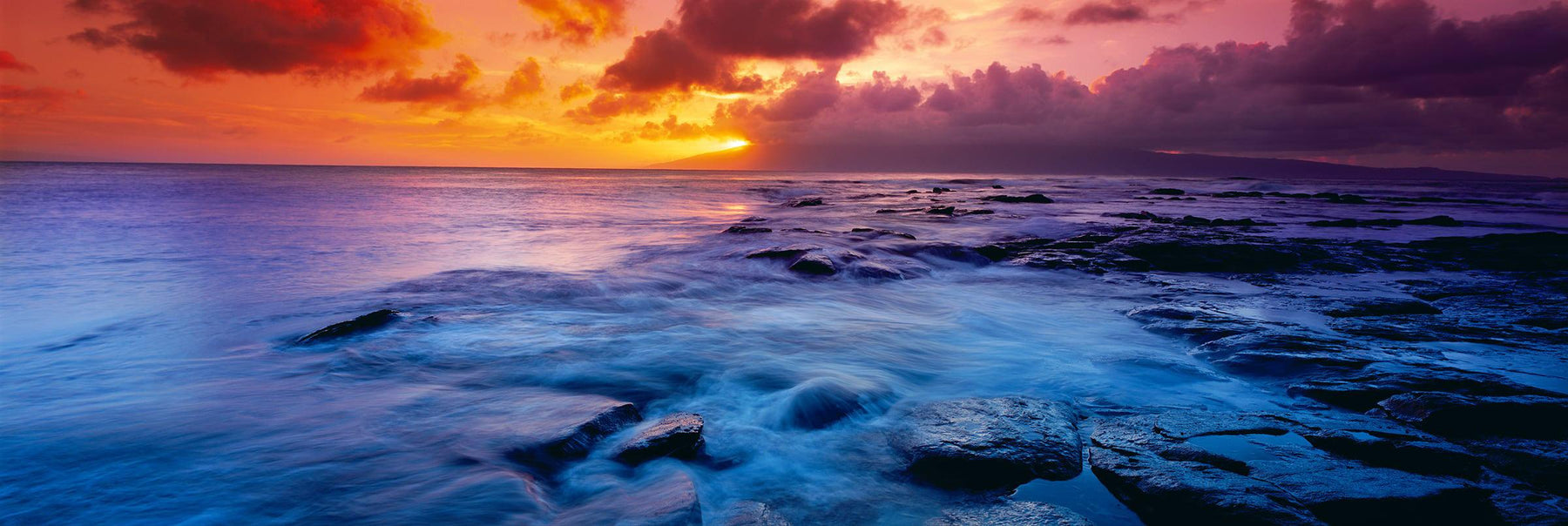 Waves washing over the black rock coast of Kapalua Bay Hawaii at sunset
