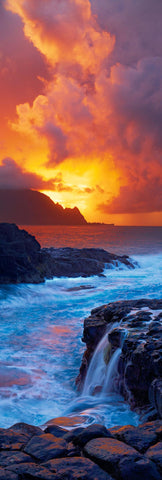 Waves crashing along the rock coast of Kaui Hawaii as the sun sets through the clouds and behind the Napali cliffs